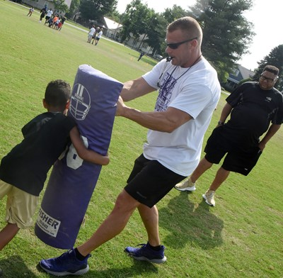CHS football assistant coach Robbie Gribbins helps Campbellsville Elementary School first-grader Kingston Cowherd as he tackles.