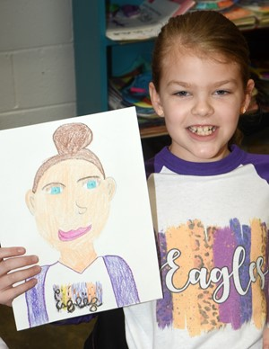 CES third-grader Zoe Weddle holds her self-portrait.
