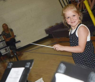 CES second-grader Ava Bennett-Marr directs the CMS/CHS band.