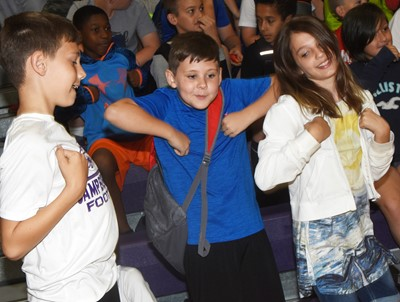 From left, CES fourth-graders Aidan Wilson, Ryan Tungate and Kairi Tucker dance as the band plays the Chicken Dance.