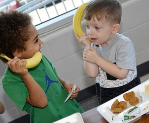 "CES preschool students Terren Lasely, at left, and Maddox Creason ""talk"" on the ""telephone."""