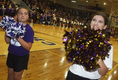 CHS senior Alli Wilson, at right, cheers with CES fifth-grader Annabelle Brockman.