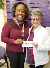 Wanda Hurt, on behalf of a group of students from the Campbellsville High School Class of 1972, at right, makes a $250 donation to Campbellsville Middle and High School Youth Services Coordinator Theresa Young.
