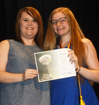 Whitney Frashure receives the scholarship award from teacher Paige Cook.