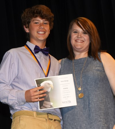 Weston Mattingly receives the scholarship award from teacher Paige Cook.