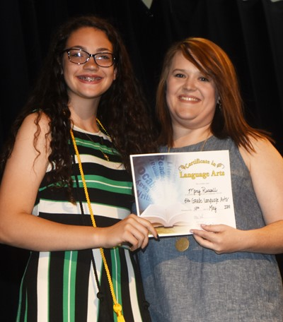 Mary Russell receives the language arts award from teacher Paige Cook.