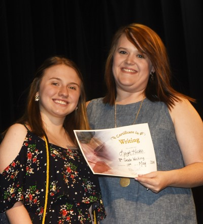 Leigh Hicks receives the writing award from teacher Paige Cook.