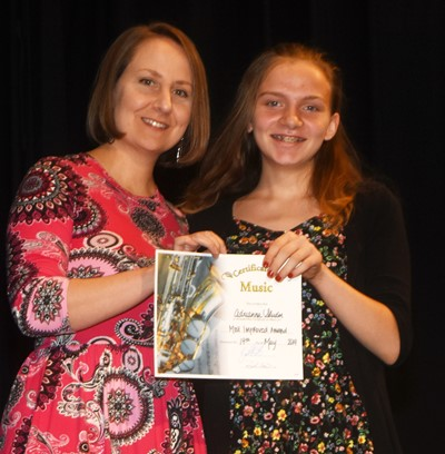 Adrianna Sluder receives the most improved music award from teacher Jessica Floyd.
