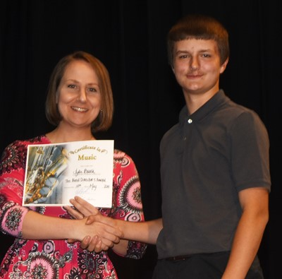 Tyler Booth receives the band director's award from teacher Jessica Floyd.