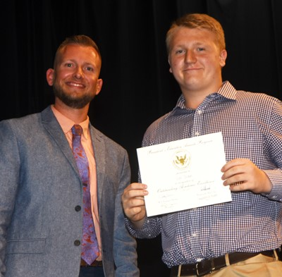Levi Dicken receives the President's Award of Educational Excellence from CMS Principal Zach Lewis.