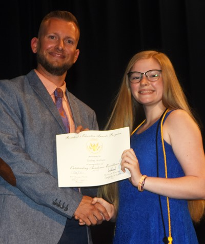 Whitney Frashure receives the President's Award of Educational Excellence from CMS Principal Zach Lewis.