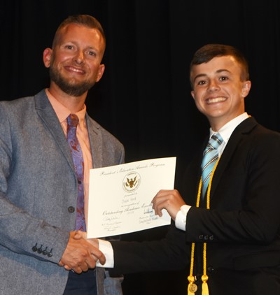 Chase Hord receives the President's Award of Educational Excellence from CMS Principal Zach Lewis.