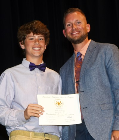 Weston Mattingly receives the President's Award of Educational Excellence from CMS Principal Zach Lewis.
