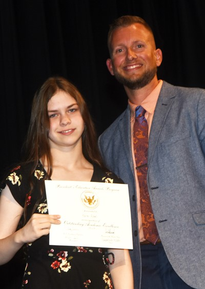 Karlee Rakel receives the President's Award of Educational Excellence from CMS Principal Zach Lewis.