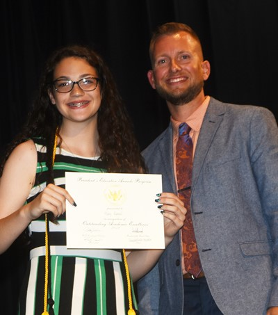Mary Russell receives the President's Award of Educational Excellence from CMS Principal Zach Lewis.