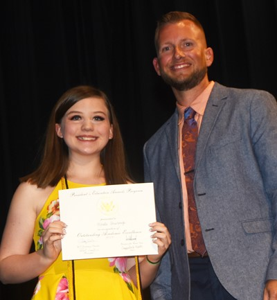 Mikaela Scharbrough receives the President's Award of Educational Excellence from CMS Principal Zach Lewis.