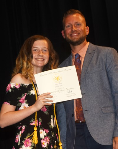 Dakota Slone receives the President's Award of Educational Excellence from CMS Principal Zach Lewis.