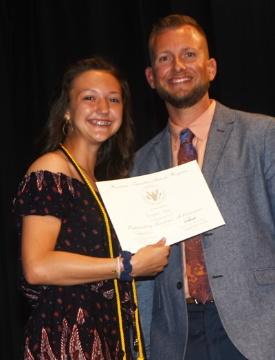 Bri Hayes receives the President's Award of Educational Achievement from CMS Principal Zach Lewis.
