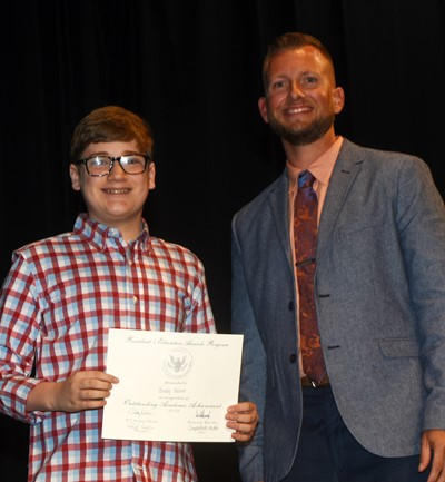 Brady Hoosier receives the President's Award of Educational Achievement from CMS Principal Zach Lewis.