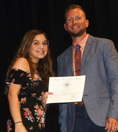 Kailey Lozano receives the President's Award of Educational Achievement from CMS Principal Zach Lewis.