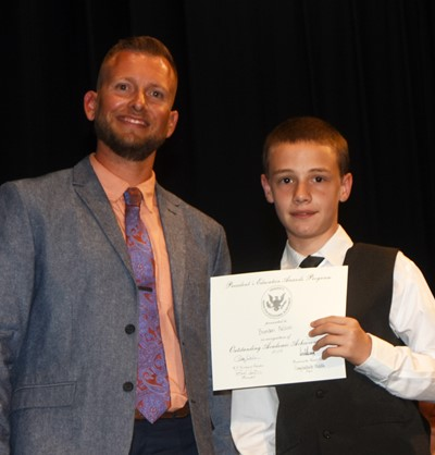 Brandon Nelson receives the President's Award of Educational Achievement from CMS Principal Zach Lewis.
