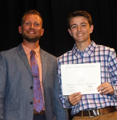 Bryce Newton receives the President's Award of Educational Achievement from CMS Principal Zach Lewis.