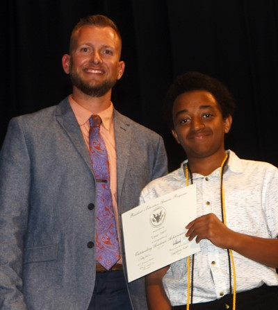 Zamar Owens receives the President's Award of Educational Achievement from CMS Principal Zach Lewis.