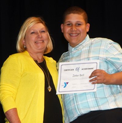 Zeke Bell is recognized for his participation in Y Club this school year. At right is co-sponsor Jan Speer.