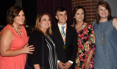 CMS eighth-grader Chase Hord smiles for a photo with teachers, from left, Robbilyn Speer, Amy Knifley, Melisa Morris and Paige Cook.