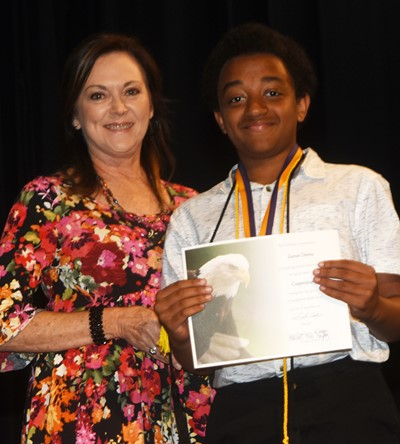 Zamar Owens receives the cooperation award from teacher Melisa Morris.