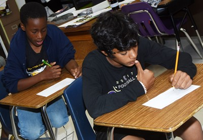 iEagle sixth-graders John Gholston, at left, and LaDainien Smith complete a quiz about bullying.