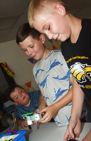 iEagle students, from left, fifth-graders Hayden Maupin, Ryan Tungate and Joseph Greer program their Lego robot.