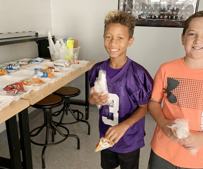 iEagle fifth-graders Rajon Taylor, at left, and Luke Adkins prepare lunches.