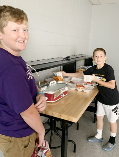 iEagle seventh-grader Levi Young, at left, and fifth-grader Lanigan Price prepare lunches.
