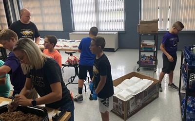 iEagle students, with help from Director of Food Service David Petett, at left, and teacher Hannah Jones, in front, prepare lunches.