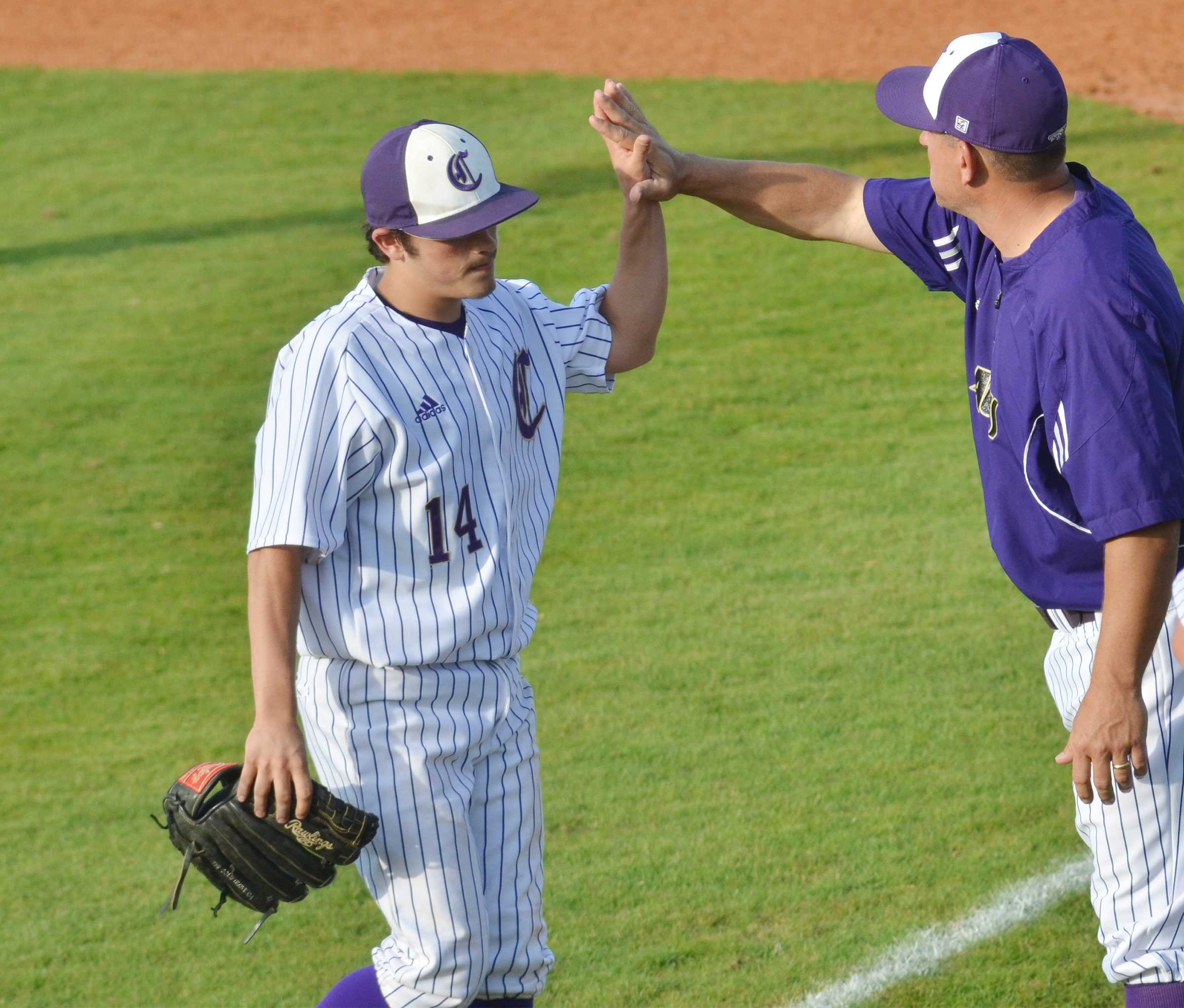 CHS head baseball coach Kirby Smith high fives sophomore Ryan Kearney after an inning.