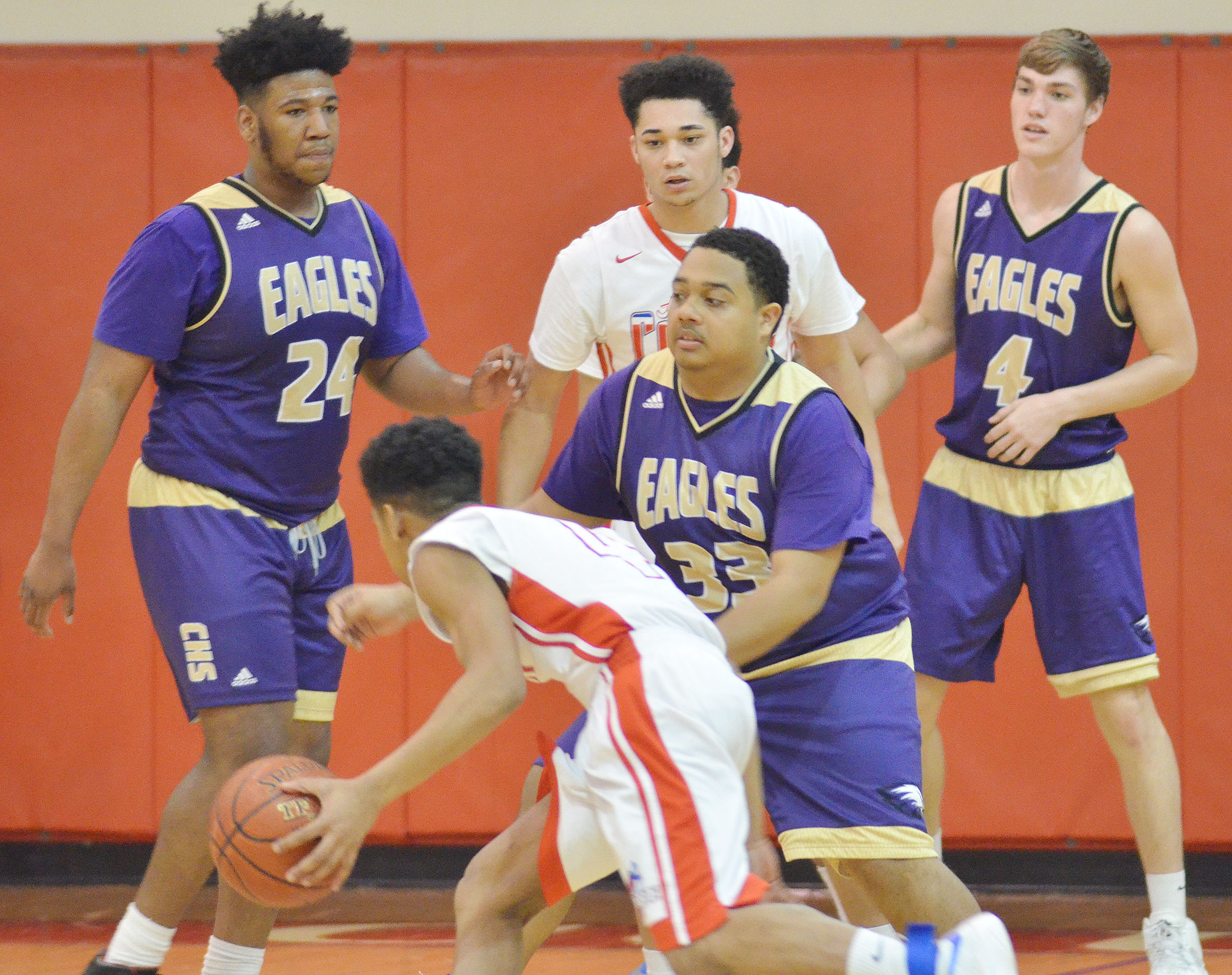 From left, CHS seniors Micah Corley, Ricky Smith-Cecil and Zack Bottoms play defense.