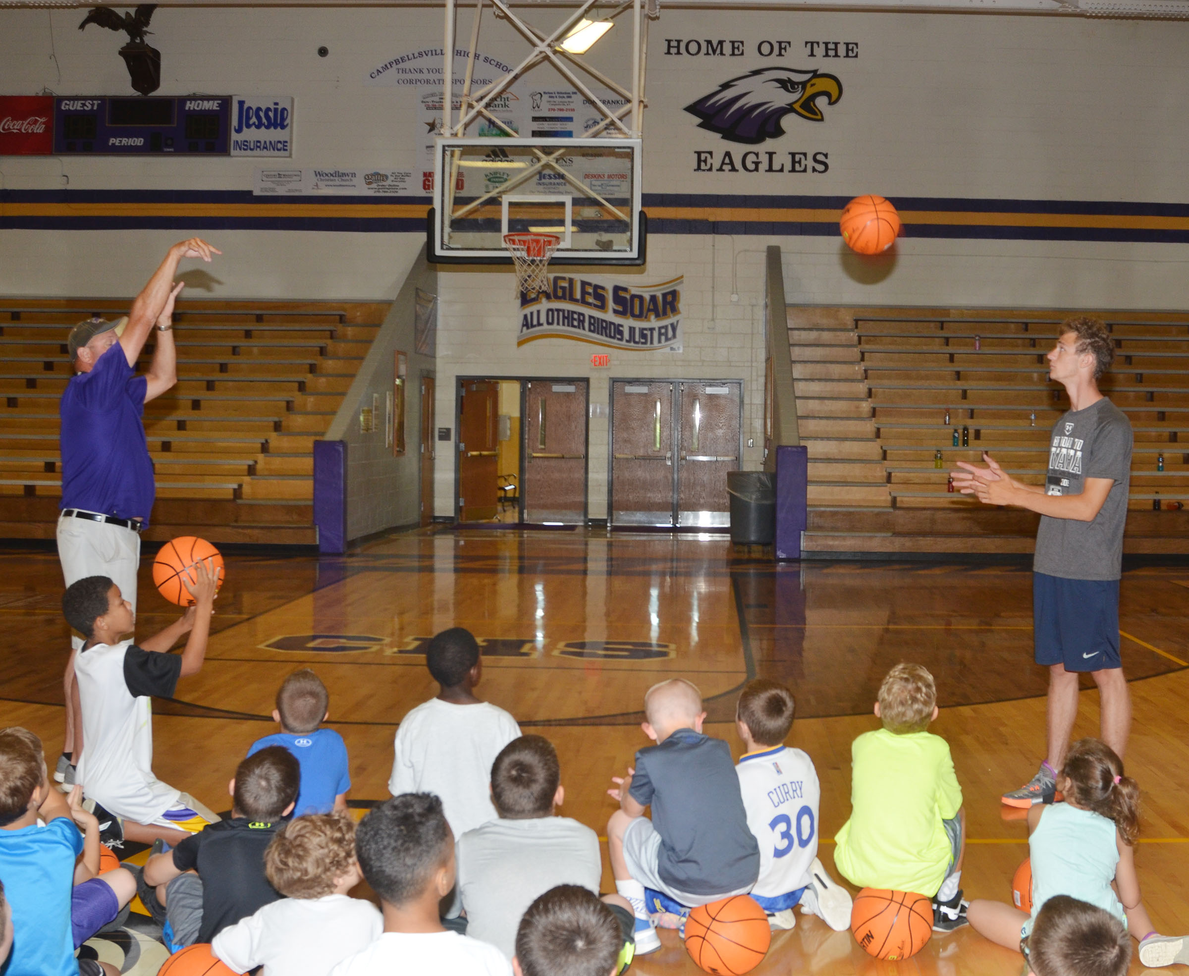 CHS boys' head basketball coach Tim Davis demonstrates a shooting technique with senior player Connor Wilson.