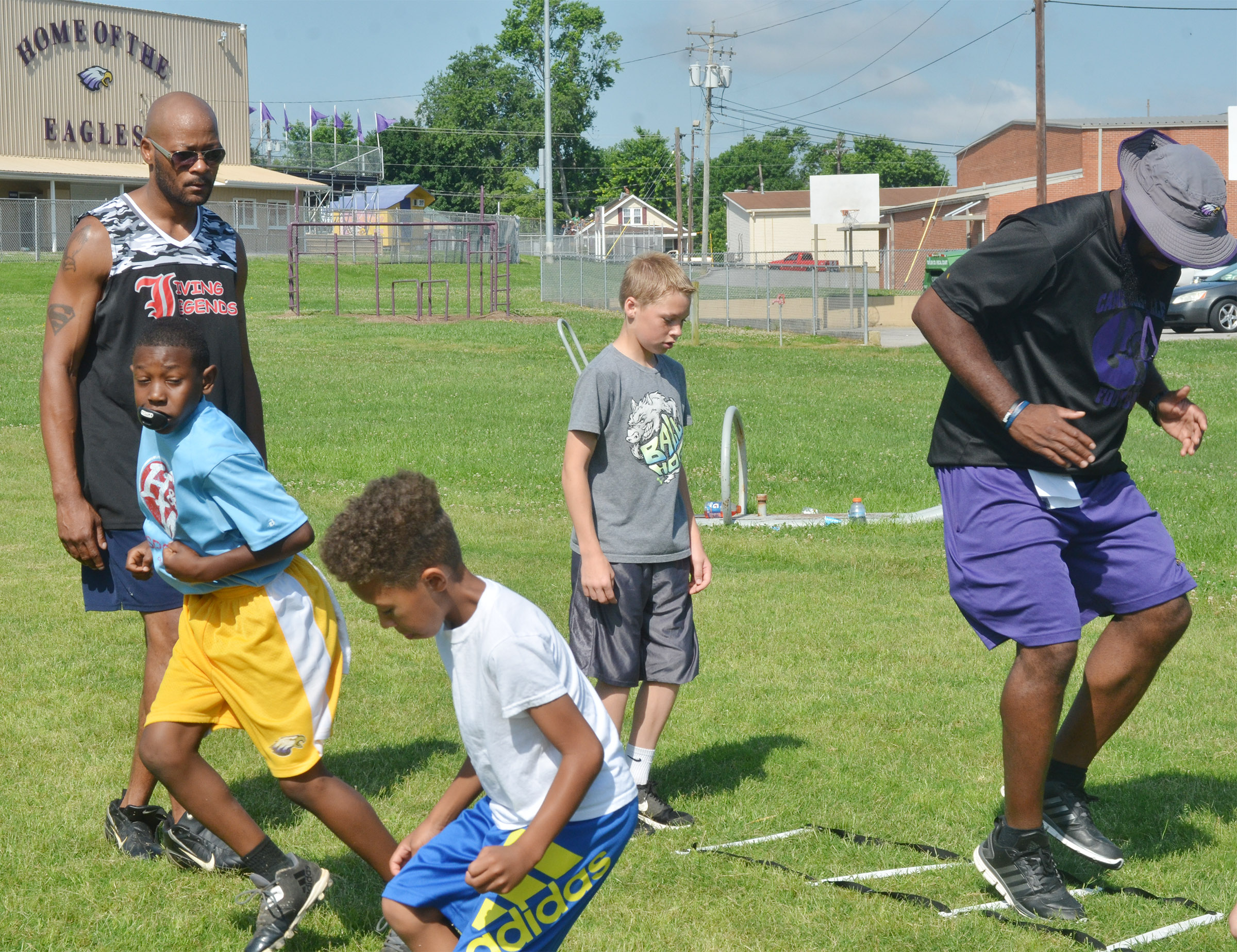 Former NFL player Tony Driver helps campers work on their footwork.