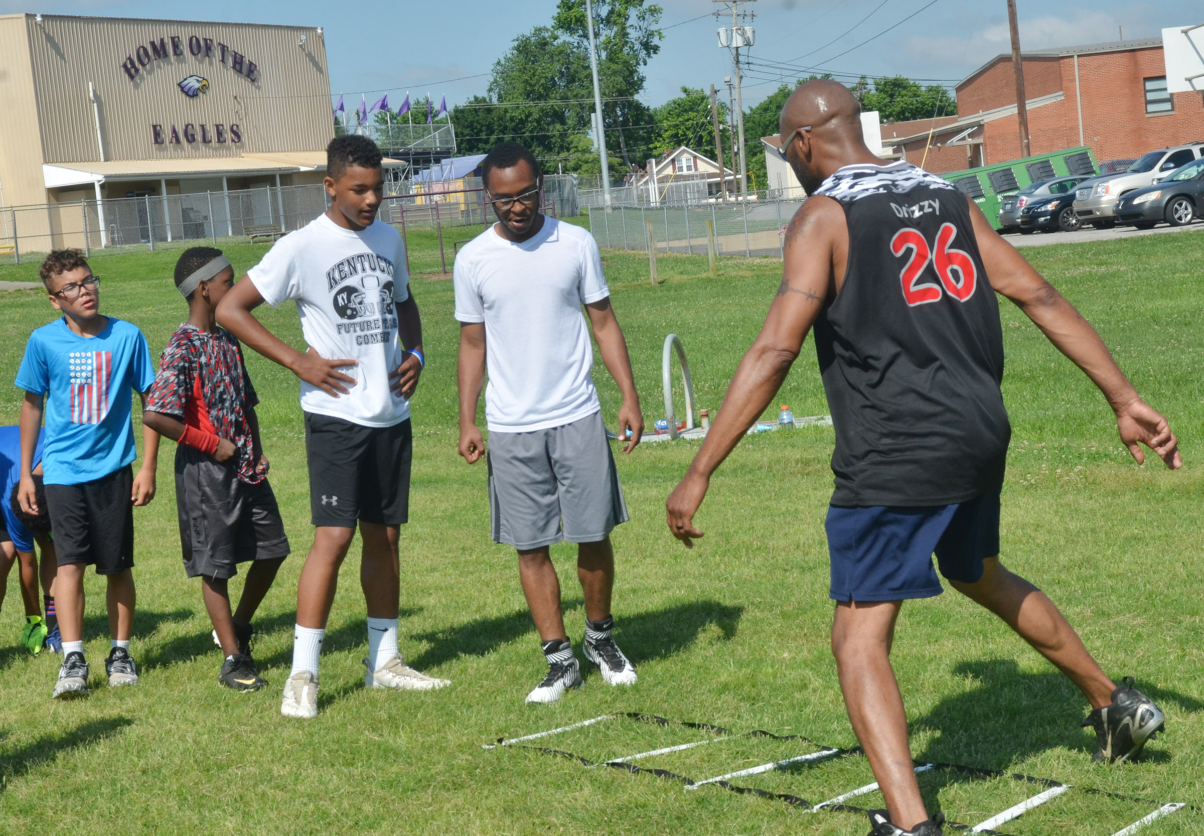 Former NFL player Tony Driver shows campers how to run a drill.
