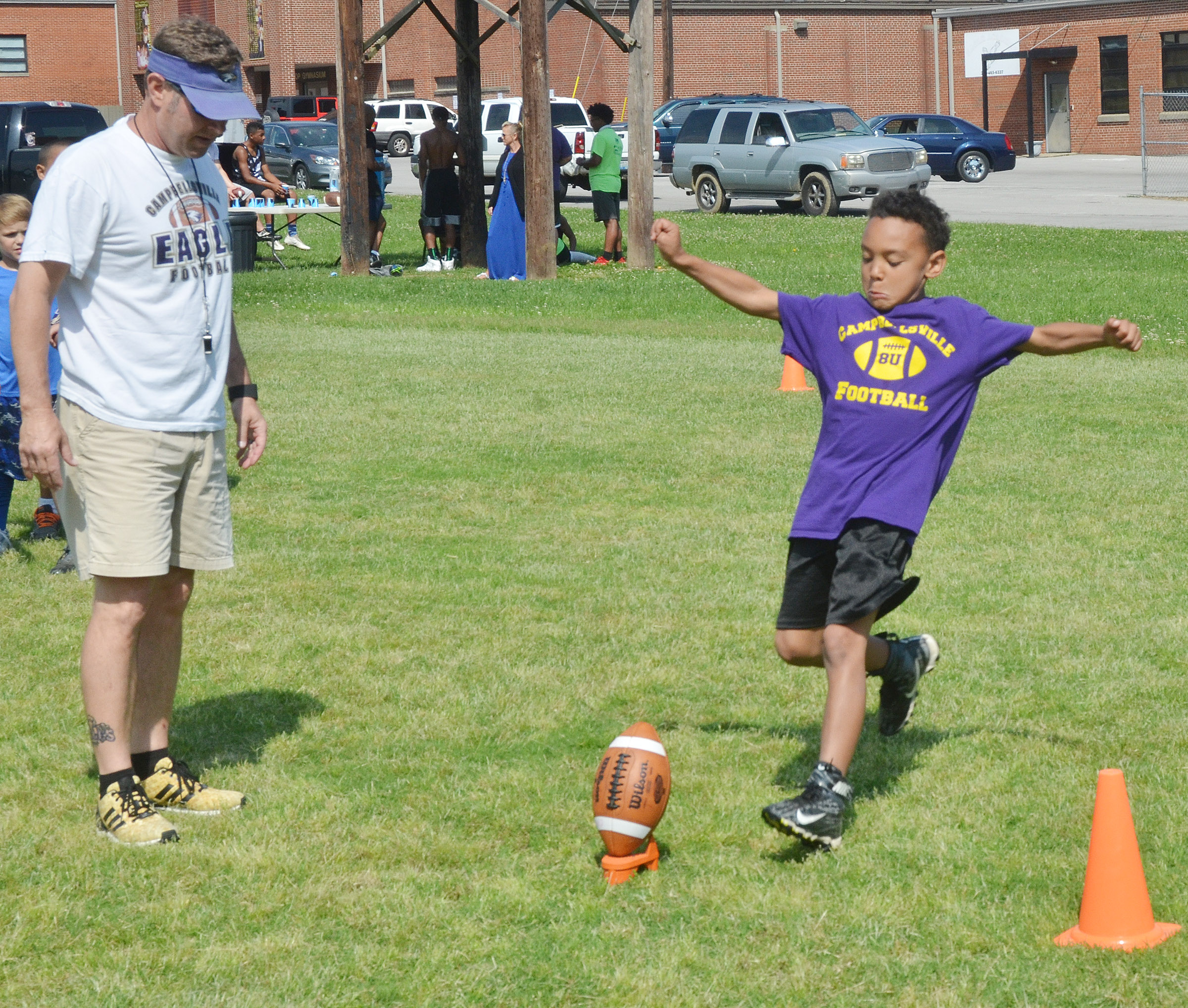 Maddox Hawkins kicks the ball, with help from assistant coach Herb Wiseman.