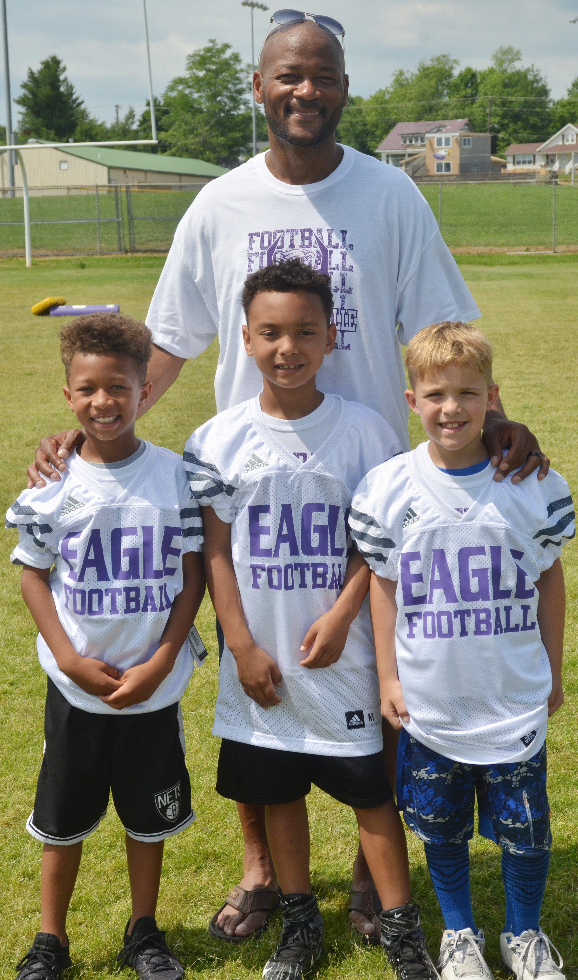 Winners of the third- and fourth-grade division are, from left, Rajon Taylor, throwing; Maddox Hawkins, kicking; and Kadin Coppage, catching. They are pictured with former NFL player Tony Driver, who worked with campers on fundamentals.