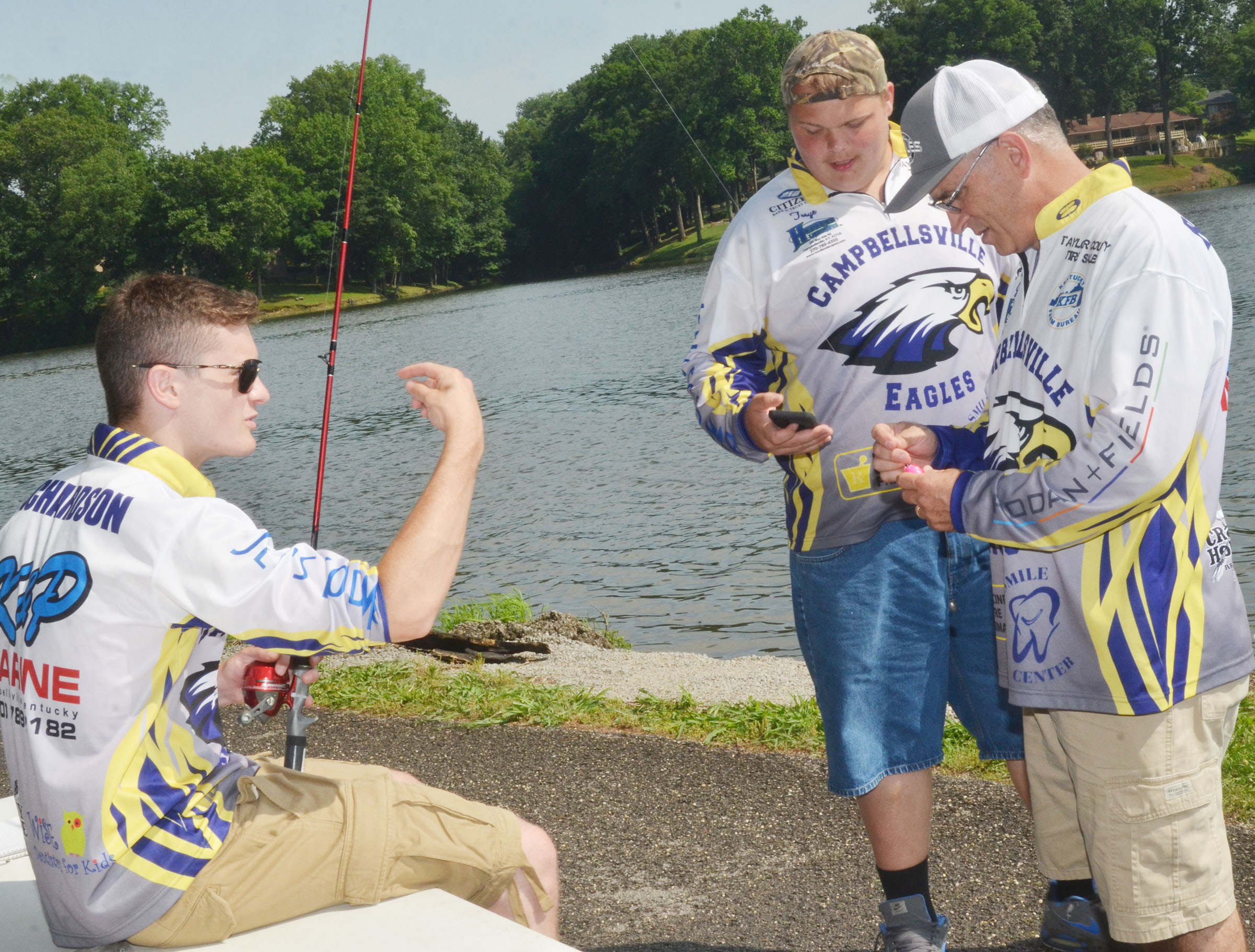CHS fishing team members Bryce Richardson, at left, and Toyse Cox, who will be seniors this fall, and fishing coach Jeff Richardson teach how to cast.