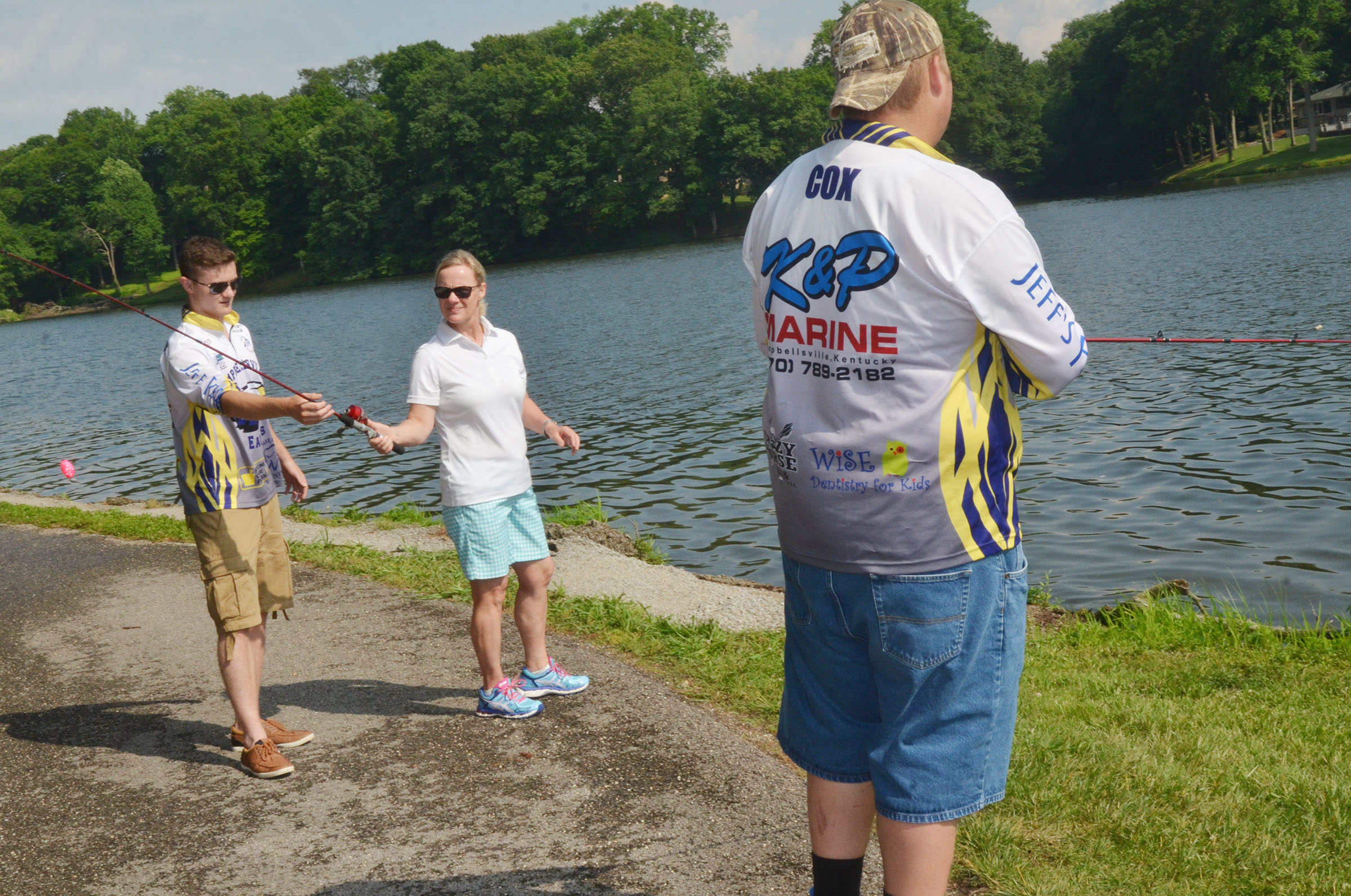 CHS fishing team member Bryce Richardson, at left, helps Mary Ann Rice learn to cast.