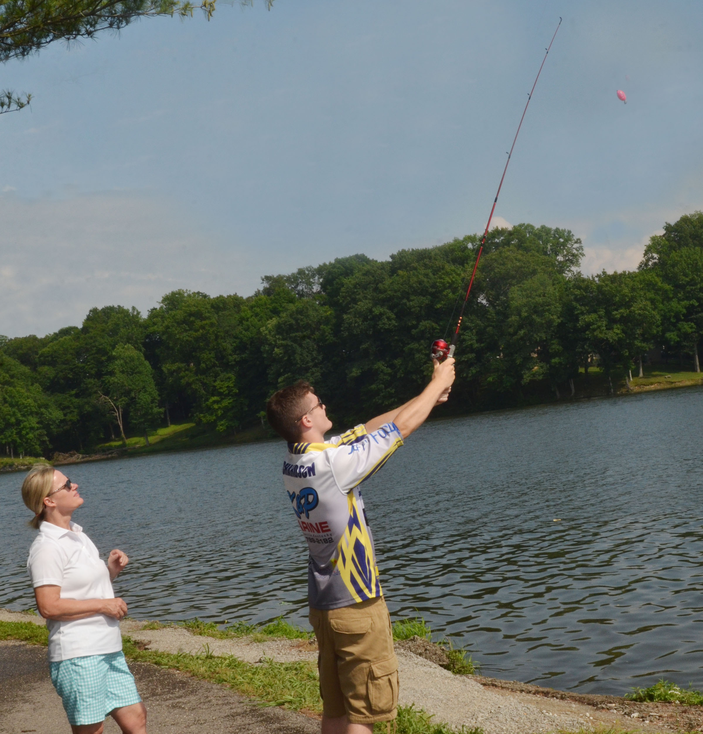 CHS fishing team member Bryce Richardson helps Mary Ann Rice learn to cast.
