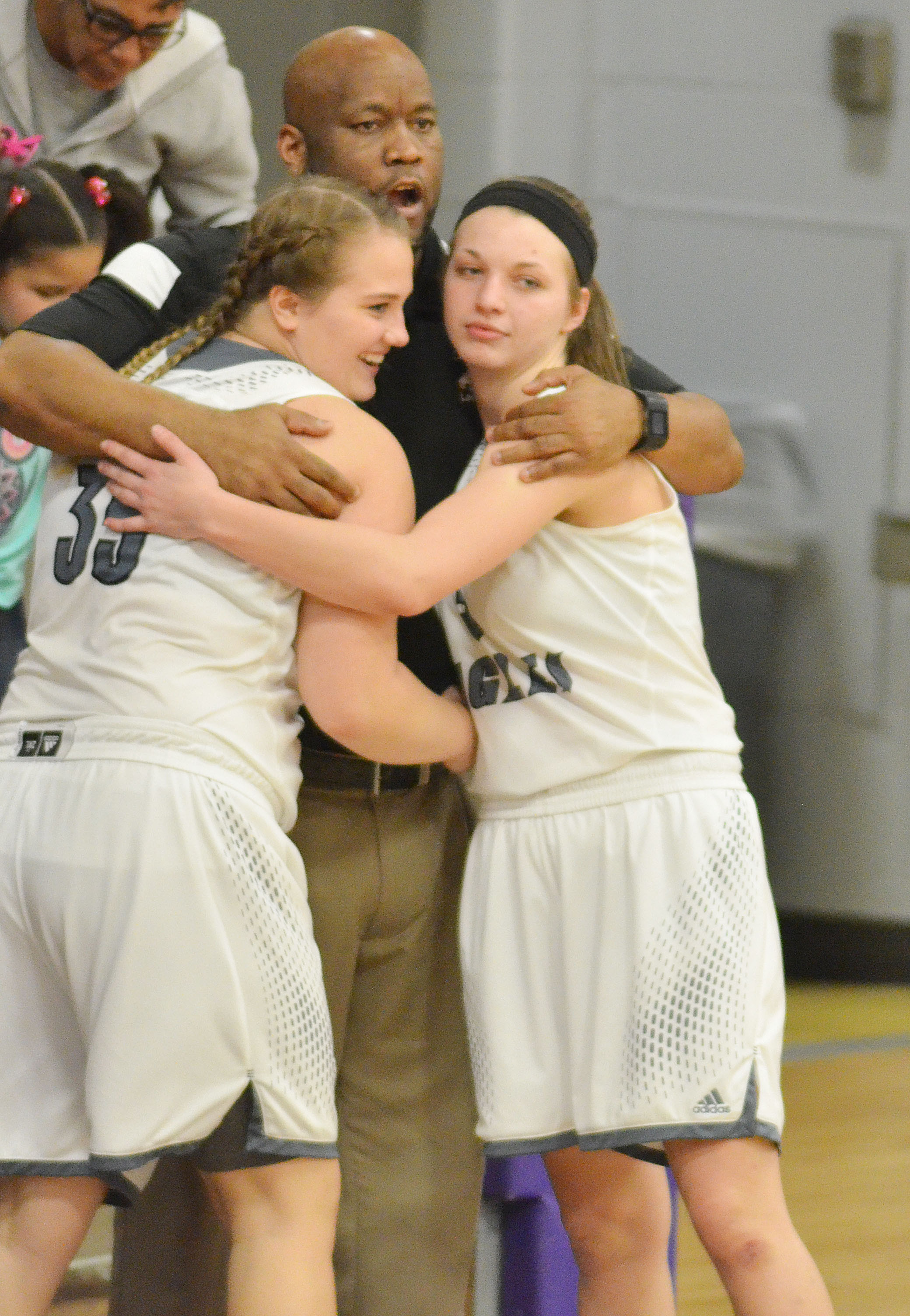 CHS girls' basketball head coach Anthony Epps hugs seniors Brenna Wethington, at left, and Caylie Blair after they play their final minutes on the Lady Eagles home court.