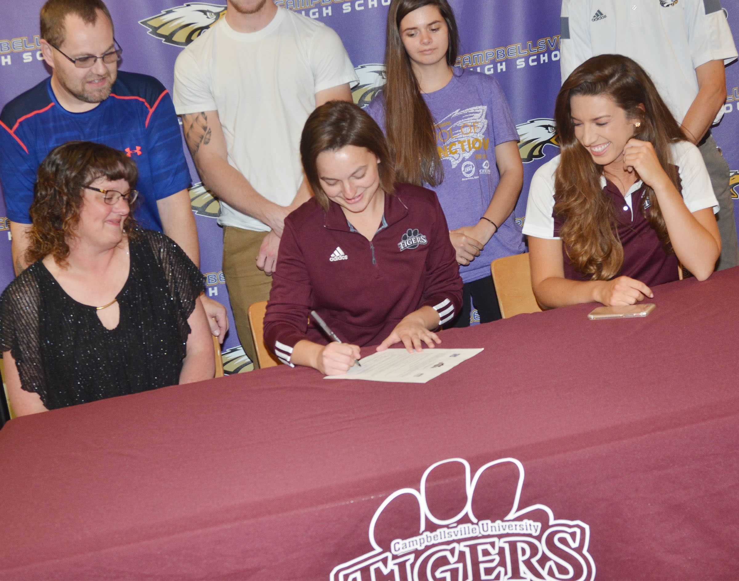 Campbellsville High School senior Kyrsten Hill will continue her academic and tennis career at Campbellsville University this fall. She recently signed her letter of intent in a special ceremony with her family, friends, teammates and coaches. From left, her parents Tonya and Jonathan Hill, teammate Shauna Jones, who is also a senior, and CU tennis coach Kristen Hamrick watch her sign.