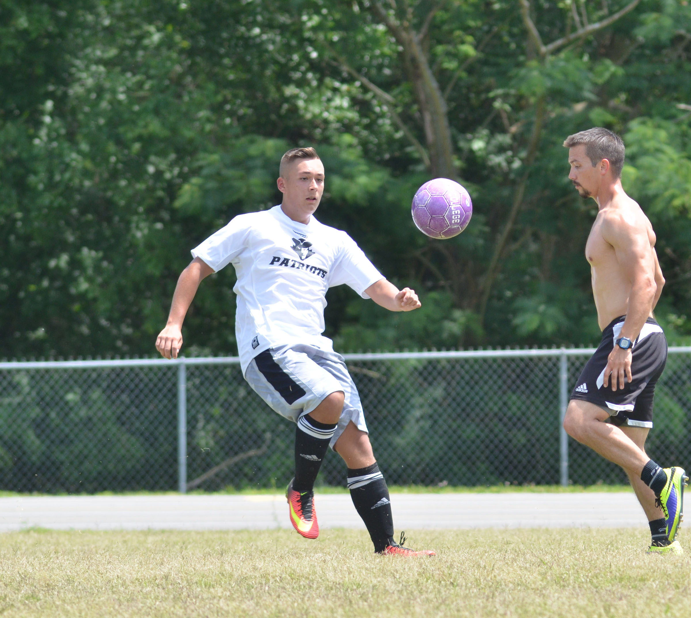 CHS senior Cody Davis, at left, kicks the ball as alumni player Drew Skaggs attempts to steal it.