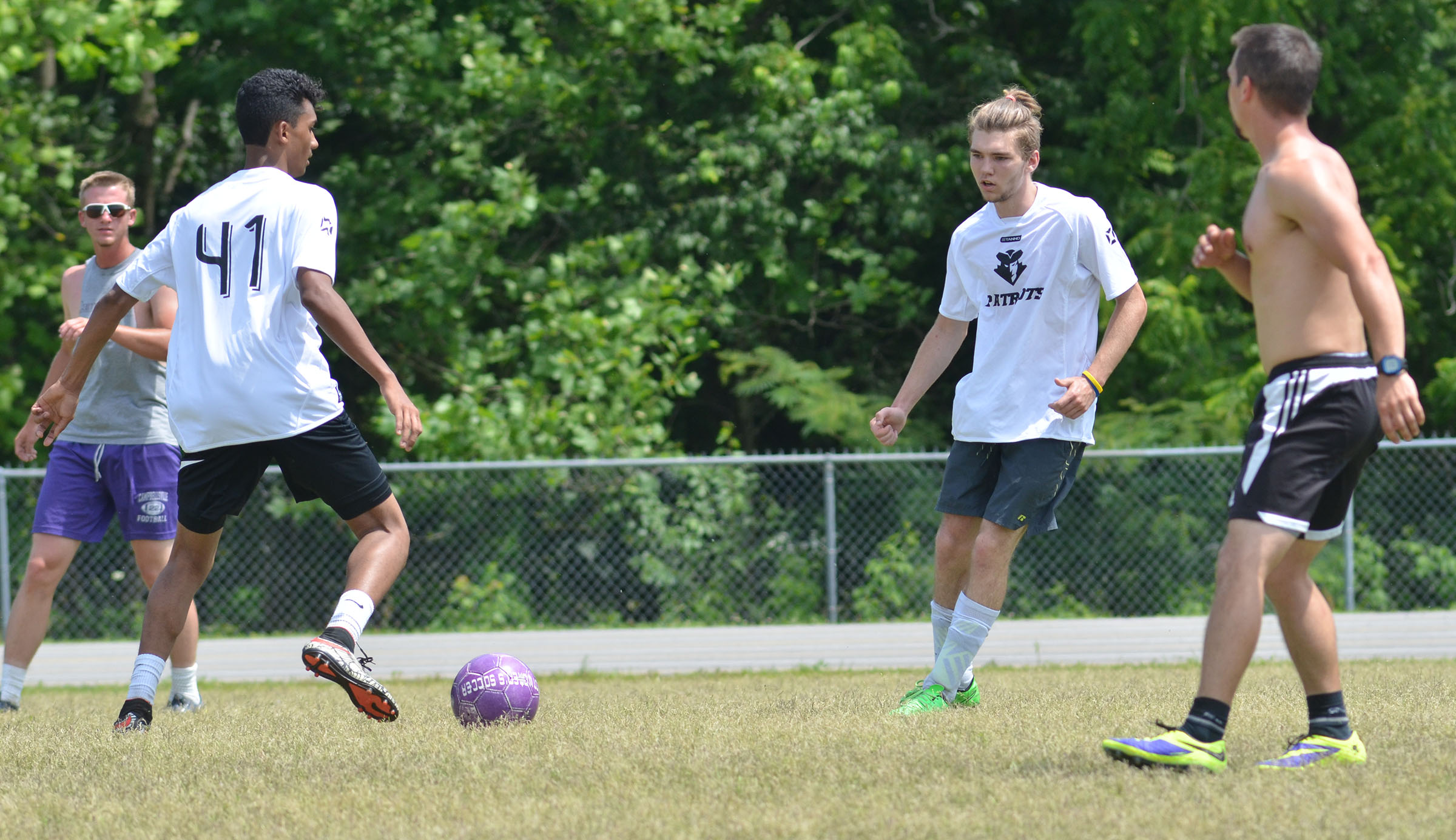 CHS soccer alumni player Daniel Silva, who graduated in May, kicks the ball to teammate Christian Berry, a senior.