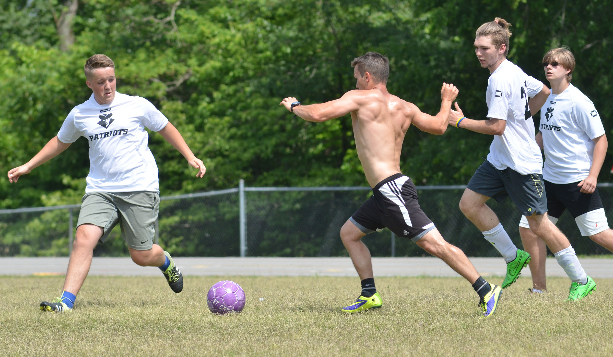 CHS soccer alumni player Drew Skaggs attempts to steal the ball from senior player Justin Richerson.